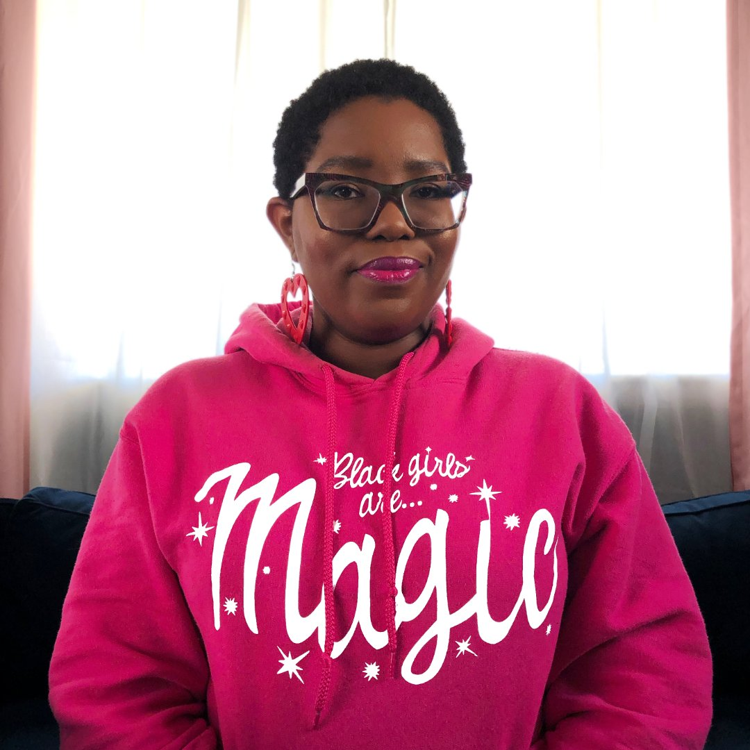 "Dominique wearing a ""Black Girls Are Magic"" Hoodie while sitting on a dark blue sofa. In front of a window with white curtains. Pink drapes on the edges."