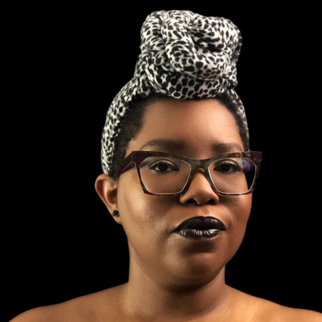Dominique is looking at the camera wearing a black and white headwrap and black lipstick. She is in front of a black background. Only her shoulders up are visible.