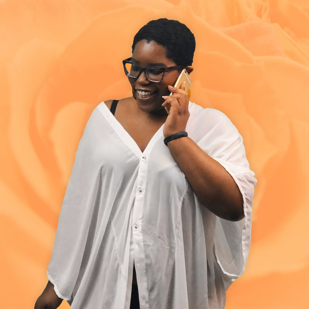 Dominique is holding a smartphone to her ear while smiling and talking. She is wearing an oversized white coverup and standing in front of a light orange background with a rose texture.